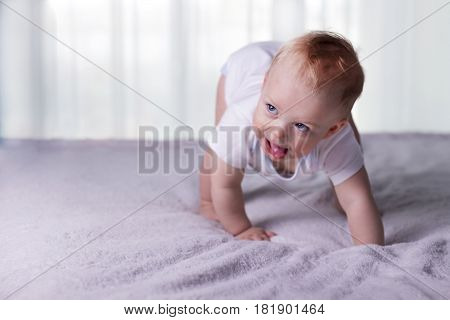 The Boy With Tongue Hanging Out Doing His First Steps. Open-eyed Infant Kid On The Bed Trying To Tod
