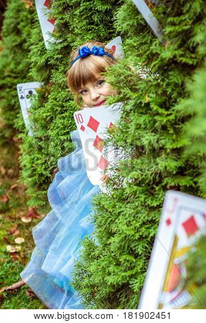 An little beautiful girl in a long blue dress in the scenery of Alice in Wonderland looking from under the fir trees are decorated with large playing cards.