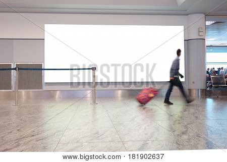 A man with suitcase walks in an airport with blank white sign behind him for copy space