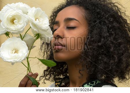 African Ethiopian young woman smelling white roses