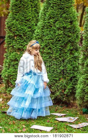 An little beautiful girl in a long blue dress in the scenery of Alice in Wonderland standing near the fir trees and looking down at the playing cards.