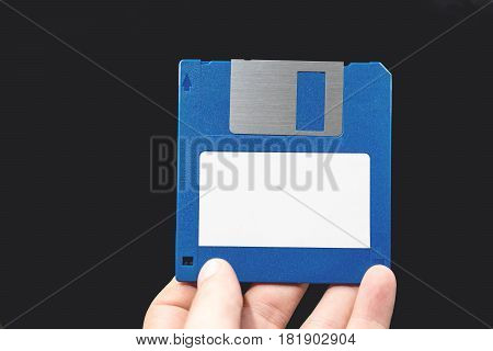 Computer Floppy Disk In Hand On Black Background.