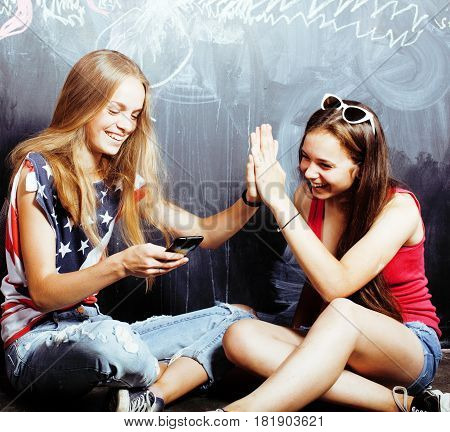 back to school after summer vacations, two teen real girls in classroom with blackboard painted together, lifestyle people concept close up