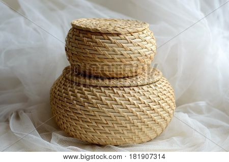 Wicker round baskets on a background of delicate tissue. Rural weaving with natural straw. Weaving from natural plants. Ecological items for the home.