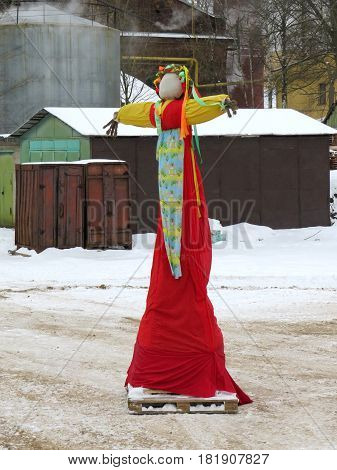 Maslenitsa (Eastern Slavic religious and folk holiday) effigy out of straw Before the festive burning on the background of the boiler house of the Polytechnic University