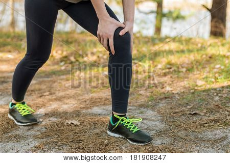 Girl in sports pants and shoes standing holding on to the knee. Knee injury