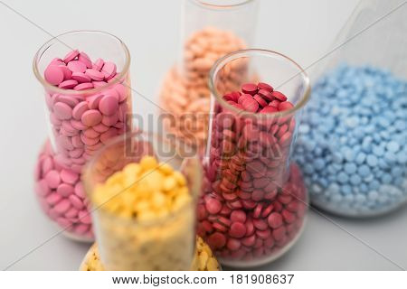 Multicolored placebo pills in the five glass flasks on the light surface. Pills are yellow, pink, orange, red, blue and have different size. Macro photo. Horizontal.