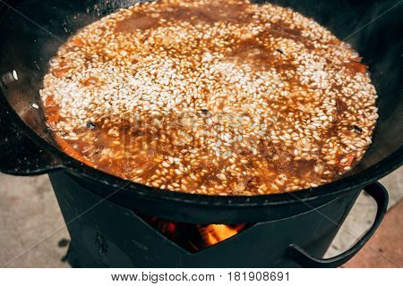 Cooking plov in the cauldron. Rice, meat, onions and carrots in a cauldron. Field kitchen. Eastern cuisine.