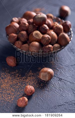 Hazelnut and cocoa powder in dark background. Ingredients for cooking homemade chocolate sweets. Confectionery and sweets concept