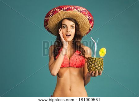 young ecstatic surprised woman on tropical vacation in beach attire and hat with exotic cocktail