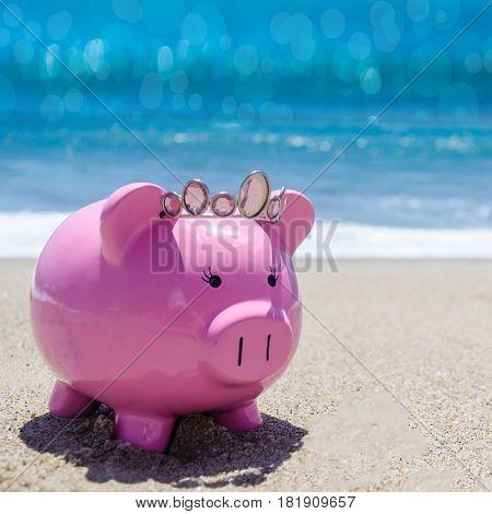 Piggy bank on the sandy beach near the ocean - square Instagram format