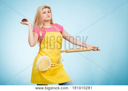 Baking tasty desserts sweets at home concept. Woman holding delicious chocolate cupcake rolling pin and colander wearing apron