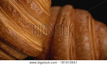 Fresh croissants on black background. Close up view. Concept of delicious food.
