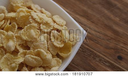 Corn flakes in white bowl with copyspace to the right. Concept of breakfast.