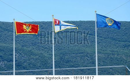 HERCEG NOVI, MONTENEGRO - JULY 25, 2016: the flag of Montenegro, adopted on 13 July 2004, the flag of Swimming Water Polo Club Jaran Herzeg Novi and the flag of Herceg Novi, are waving in the sky