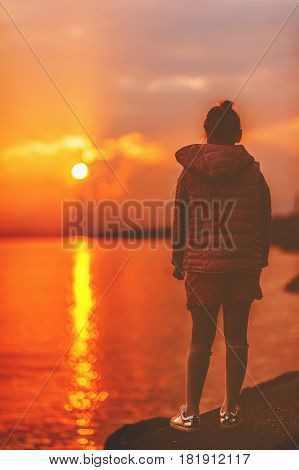 Kid girl admire amazing sunset over lake Geneva, Lausanne, Switzerland. Back view, matte image