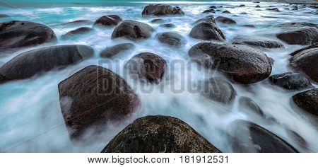 Movement of water on the shores of cold Norwegian Sea at evening time. Lofoten islands. Beautiful Norway landscape. Panoramic photo.