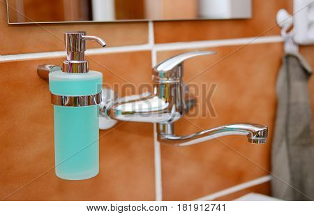 Closeup of a Soap Dispenser and Other Equipment in Bathroom.