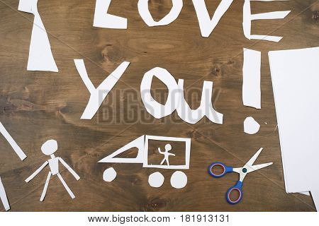 boy makes origami - car and family, children, parent, I love you text, top view on wood background