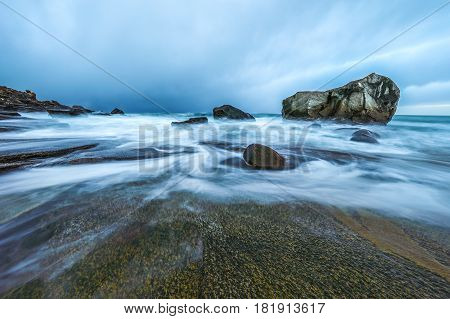 Ancient stones on the shores of cold Norwegian Sea at evening time. Lofoten islands. Beautiful Norway landscape.