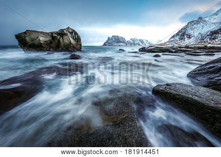 Movement of water on the shores of cold Norwegian Sea at evening time. Lofoten islands. Beautiful Norway landscape.