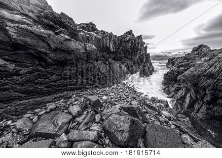 Ancient stones on the shores of cold Norwegian Sea at evening time. Lofoten islands. Beautiful Norway landscape. Black-white photo.