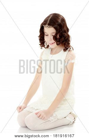 Beautiful little girl with long, dark curly hair , in a long white beautiful dress. The girl sat on her knees on the floor. Close-up.Isolated on white background.
