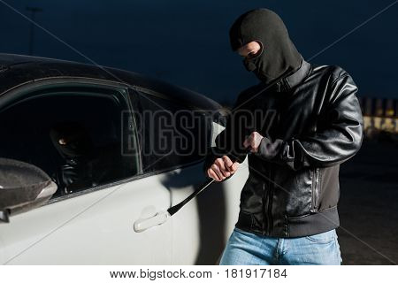 Male car thief open door with jemmy