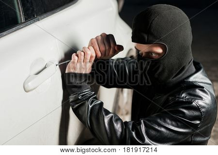 Male thief hands open car door with screwdriver