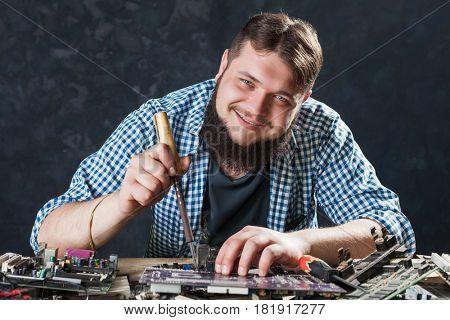 Repairman fixing problem with soldering tool