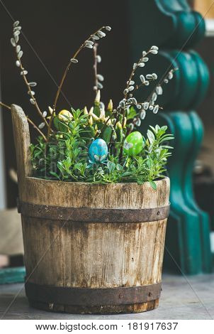 Europe street Easter decoration. Green plants, colored eggs and willow tree branches in rustic wooden tub