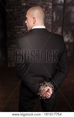 Silent assassin with hands in iron chain