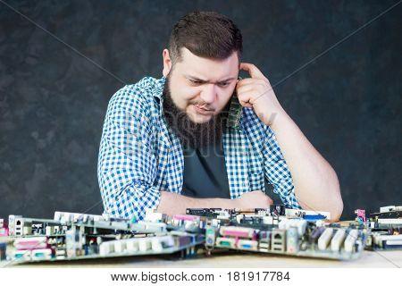Engineer work with broken computer motherboard