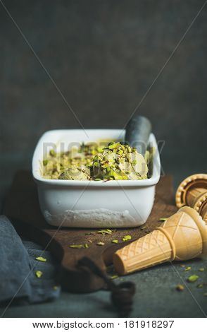 Homemade pistachio ice cream in ceramic mold with metal scooper, crashed pistachio nuts and waffle cones over concrete background, copy space