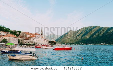 The old town of Perast on the shore of Kotor Bay, Montenegro. The ancient architecture of the Adriatic and the Balkans. Boats and yachts on the dock.