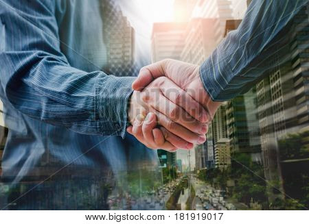 Business people shaking hands of city and sunshine