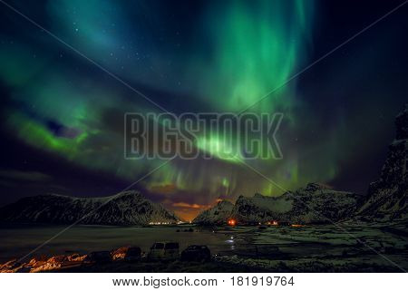Amazing multicolored green Aurora Borealis also know as Northern Lights in the night sky over Lofoten landscape Norway Scandinavia.