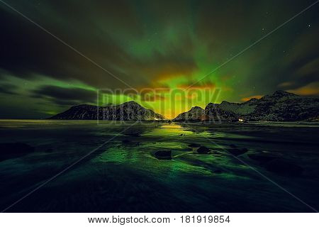 Amazing multicolored green Aurora Borealis also know as Northern Lights in the night sky over Lofoten landscape Norway Scandinavia. poster