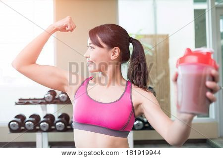 sport woman smile happiy and hold protein in the gym