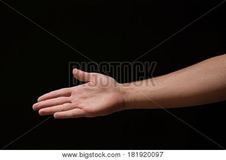 Right Hand Extended Male Arm With Open Palm On A Black Background