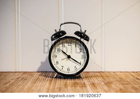 Alarm clock with 10 O'clock and twenty minuet, on wooden table and white wall