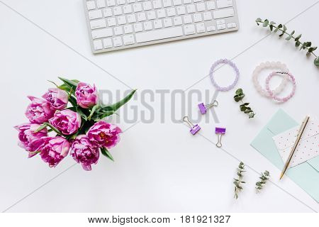 Work desk with spring flowers in home office concept on white background top view