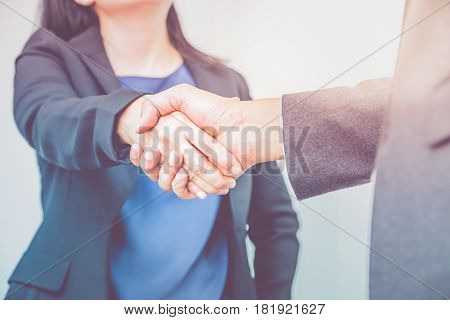 Close up businesswoman and businessman shaking hands Business partnership conceptFilter color effect.
