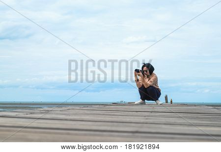 Asian Woman Traveler Take Photo Of Seascape On Wood Bridge With Blue Sky And Ocean At Background,low