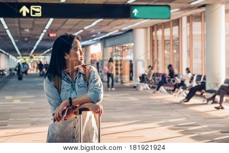 Woman traveler looking out of window and waiting with suitcases at airport departure terminal walk way to gateTransportation travel concept.
