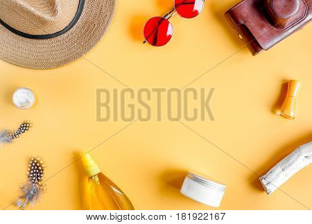 cream and lotion cosmetic for sun protection, camera hat and glasses in a woman hygiene concept on orange background top view mockup
