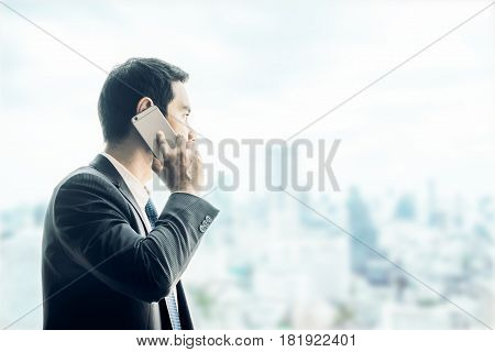 Businessman using mobile phone looking through office window to see cityscape building outsideBusiness vision conceptimgae tone filter.