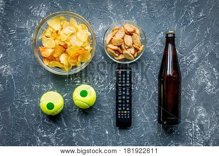 watching sport football match set with chips on dark desk background top view