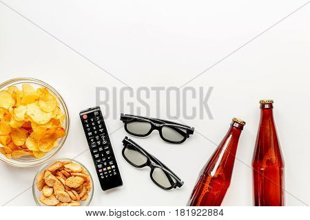 snacks for watching TV film with glasses and control on white desk background top view mock-up