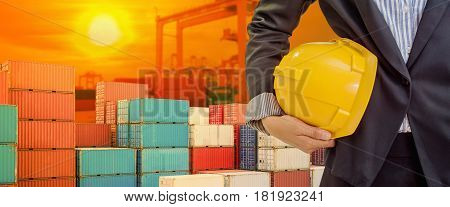 person holding yellow helmet for workers security on industrial port background and light shines sunset